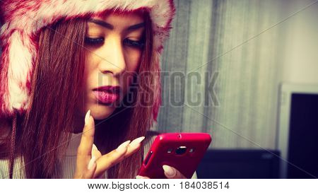 Digital technology people concept. Young woman with cell phone. Attractive girl has red fur cap on her head.
