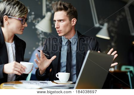 Contemporary brokers discussing new financial changes while having coffee in cafe