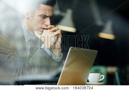 Tense trader looking at laptop display while reading data