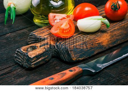 Fresh tomatoes, sliced onion bulbs on rustic wooden cutting board and olive oil in cruet on old dark wood table. Close-up angle view