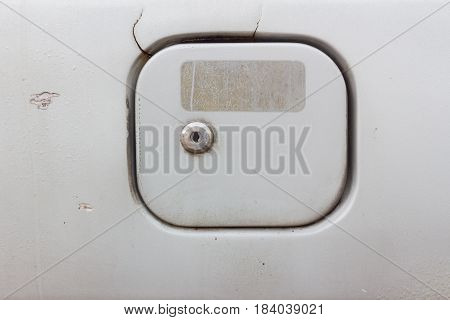 close-up fuel filler cover of old gray car with key hole and rectangular sticker stain