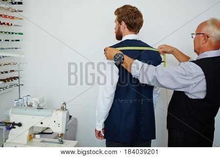 Old fashioned tailor measuring back of client in small atelier studio to make custom classic suit with jacket