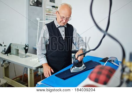 Portrait of elegant gray haired man ironing clothes in old fashioned tailoring studio with antique iron