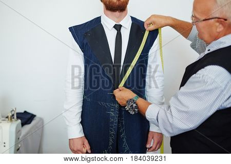 Old fashioned tailor measuring model in small atelier studio to make custom classic suit with jacket