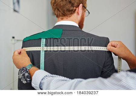 Old tailor taking back measurements from client in small atelier studio to make suit with jacket
