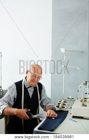 Portrait of old man working in tailoring studio making clothes at sewing machine and cutting cloth