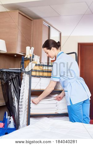 Young hotel concierge putting clean towels in stacks