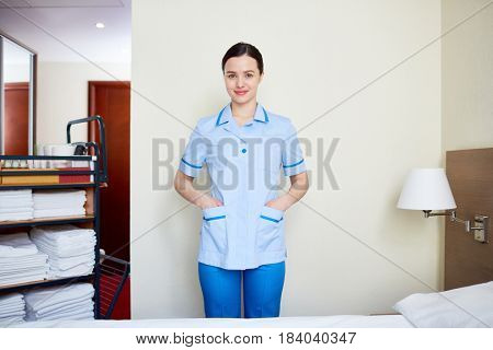 Happy young chambermaid and cart with clean towels near by