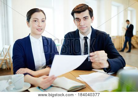 Young staff sitting by workplace and looking at camera