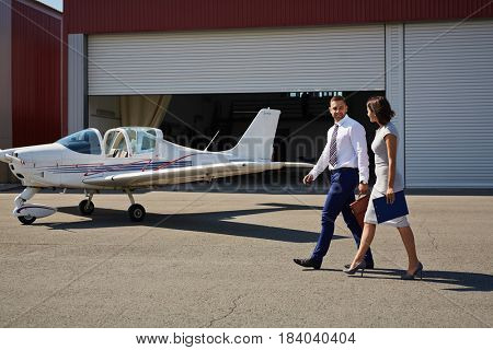 Portrait of two smiling business people, man and woman, walking by plane hangar in airport field