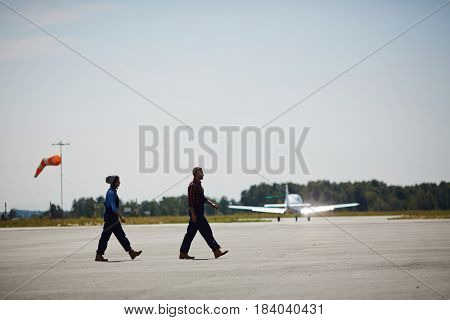 Wide shot image of two airport workers crossing runway field with plane flying up in background