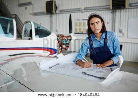 Portrait of modern woman working with engineering plans and looking at camera in airplane hangar