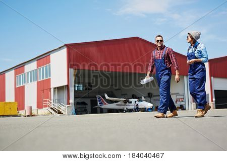 Low angle portrait of two modern mechanics, man and woman, walking in airport field with plane hangar in background