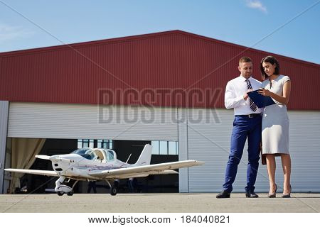 Portrait of business people in airport field: businessman signing papers before flying personal jet plane