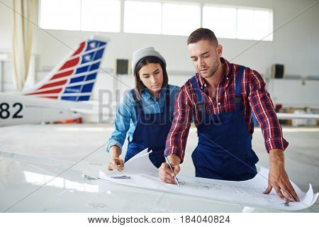 Two modern aircraft engineers, man and woman, reading blueprints in airport hangar