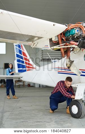 Airplane service crew repairing plane in hangar:  two young mechanics, man and woman, checking jet plane systems