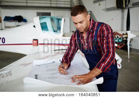 Handsome aircraft engineer reading blueprints while repairing plane in hangar