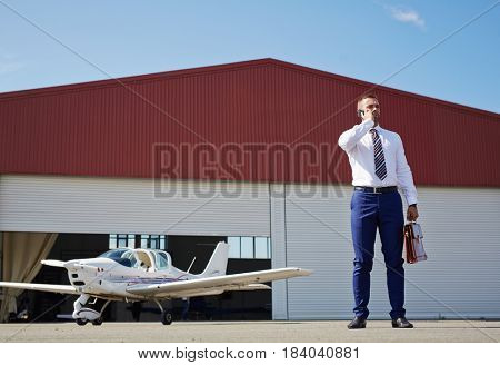 Portrait of modern businessman speaking by phone in airport field, waiting for his personal plane