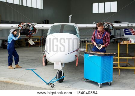 Airplane service crew working on preflight maintenance:  two young mechanics, man and woman, inspecting jet plane in hangar