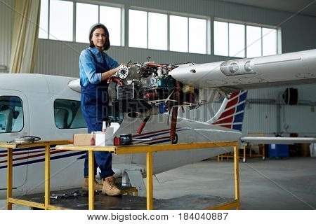 Portrait of modern young woman wearing overalls repairing jet plane turbine in hangar and smiling