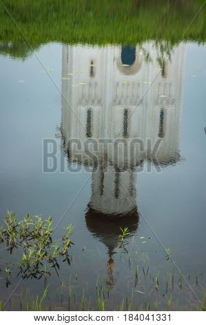 Image of reflection of white church with blue domes and scenic clouds, Bogolubovo, Russia