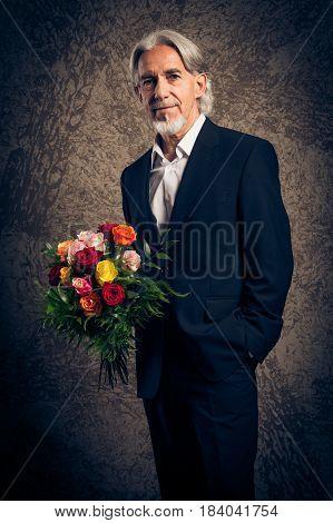 Senior man with bouquet of roses, studio portrait
