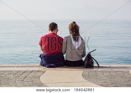 vacation, love and people concept - happy teenage couple sitting and hugging on river berth at summer .