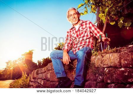 winemaker sitting on stone wall by his vineyard. backlit by the setting sun, some lens flare.