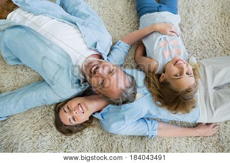 Happy father with his son and daughter lying on carpet in living room at home