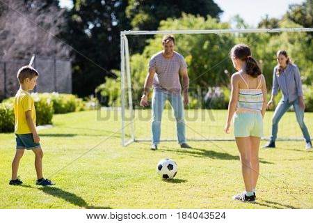 Happy family playing football together at the park