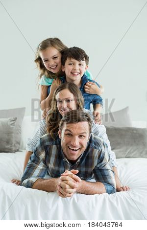 Portrait of smiling family playing on bed in bedroom at home