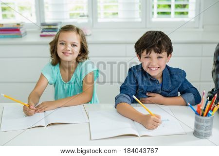 Portrait of smiling siblings studying together in living room at home