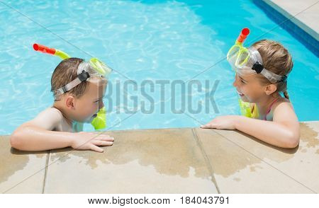 Smiling boy and girl relaxing on the side of swimming pool