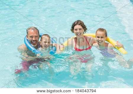 Portrait of happy parents and kids having fun in pool on a sunny day