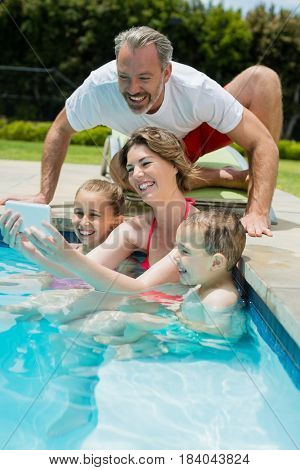 Woman taking selfie with family in swimming pool