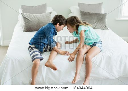 Angry brother and sister face to face on bed in bedroom at home