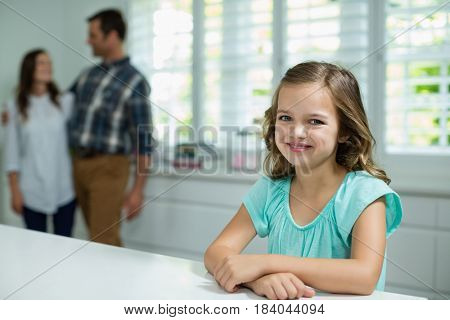 Portrait of smiling girl sitting in living room at home