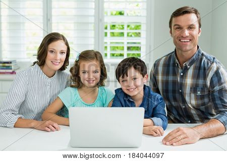 Portrait of smiling family using laptop in living room at home