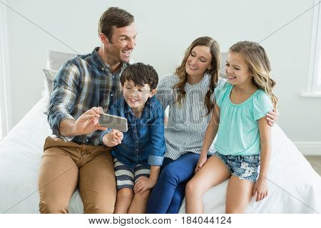 Smiling man taking selfie with family while sitting in bedroom at home