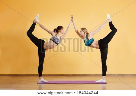 Two young sportswomen doing exercises in gym