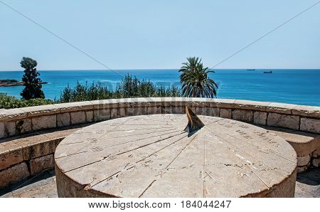 Roman sundial vintage large round stone on a hill above the sea in Sunny cloudless day