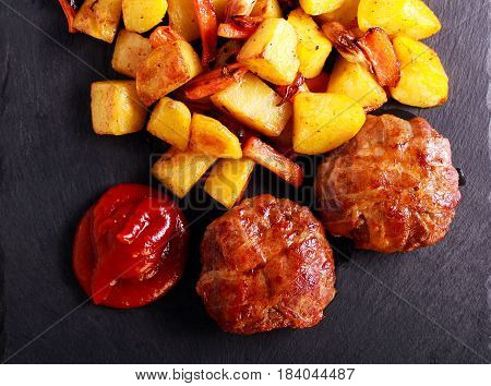 Roasted beefsteaks and potatoes with carrot on black board
