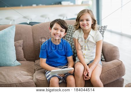 Portrait of smiling siblings using digital tablet on sofa in living room at home