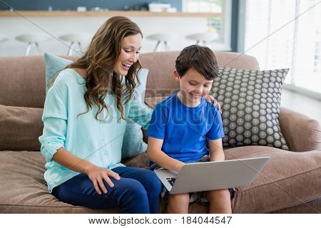Smiling mother and son sitting on sofa using laptop in living room at home