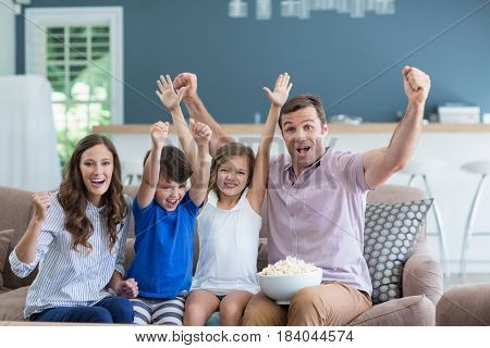 Smiling family cheering while watching tv in living room at home