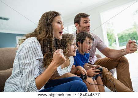 Excited family playing video games together in living room at home