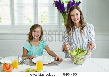 Portrait of smiling mother and daughter mixing bowl of salad in kitchen at home