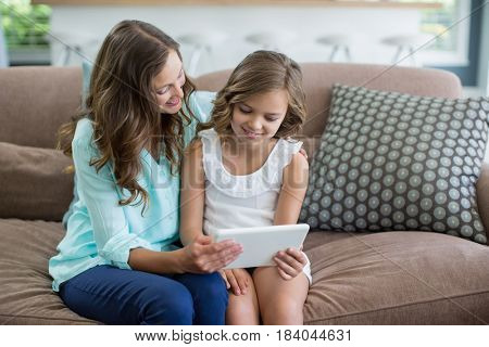 Smiling mother and daughter sitting on sofa using digital tablet in living room at home