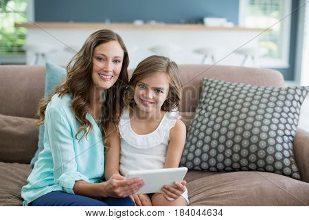 Portrait of smiling mother and daughter sitting on sofa using laptop in living room at home
