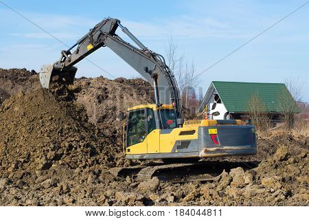 LENINGRAD REGION, RUSSIA - MARCH 09, 2017: Yellow crawler excavator is working on dumping of soil